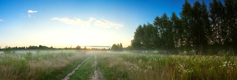 Panorama summer landscape with  blue sky, fog and the road Stock Photos