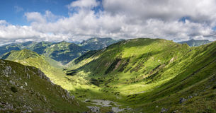 Panorama of summer mountains valley and neighbouring peaks Stock Photos
