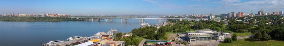 Panorama of summer Novosibirsk Octyabrsky bridge across the river Ob. Novosibirsk, Russia - July 20, 2013: Panorama of summer Novosibirsk Octyabrsky bridge Royalty Free Stock Photography