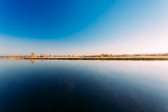 Panorama of sun rises over river. Autumn frost frozen river covered Stock Photos