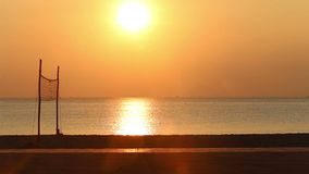 View of sunrise above beach with volleyball net. Panorama of sunrise above beach of city resort with volleyball net against sunlight path stock footage