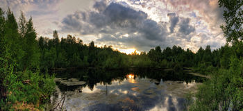 Panorama of sunset above Gloomy spring lake Stock Images