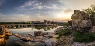Sunset over a chinese style castle in a lake with a bridge and rocks in the foreground. Beautiful clouds at sunset over a chinese style castle in a lake with a stock photo