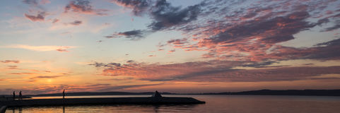Panorama of sunset on lake and people silhouettes. People silhouettes on Onego lake quay at sunset in summer season. Panoramic photo Stock Images
