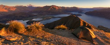Panorama at sunset of Roys Peak between Wanaka and Queenstown with a lake and Mount Aspiring and cook of the new zealand alps. royalty free stock photo