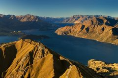 Panorama at sunset of Roys Peak between Wanaka and Queenstown with a lake and Mount Aspiring and cook of the new zealand alps. stock image