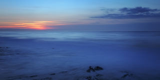 Panorama of the sunset in the sea, in cold tones and water in the form of milk. Portugal. Stock Photos