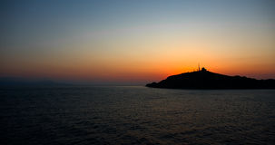 Panorama of a sunset. Sun setting behind an island in the distance. It is almost dark royalty free stock photos