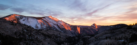 Panorama of sunset at Yosemite and Half Dome. Panorama view of sunset in Winter at mountain range with Half Dome in Yosemite National Park Royalty Free Stock Photos