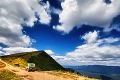 Panorama SUV op de mooie achtergrond van het berglandschap Royalty-vrije Stock Foto's