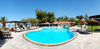 Panorama of swimming pool by beach Stock Images