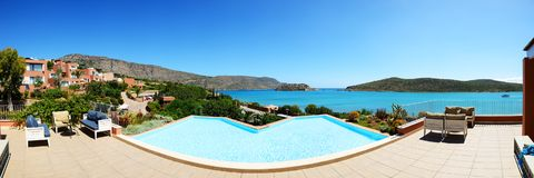 Panorama of swimming pool at luxury hotel with a view on Spinalonga Island Stock Photos
