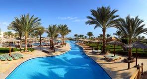 Panorama of swimming pool at resort. Panorama of swimming pool with palm trees at resort Stock Photography