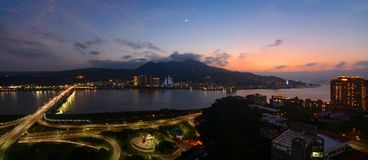 Panorama of the Tamsui and Bali districts along the river in New Taipei City at sunset with a crescent moon and the planet Venus r stock photography