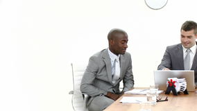 Panorama of three businessmen in a meeting. Panorama of two caucasian and an AfroAmerican businessmen in a meeting working with a laptop. Footage in high stock footage