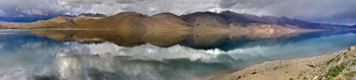 Panorama of a thunderous evening at the high mountains of Lake Tso Moriri: perfectly flat water surface reflects the chain of hill Royalty Free Stock Images