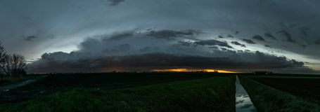 Panorama of a thunderstorm over the dutch landscape after sunset. stock photo