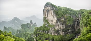 Panorama of the Tianmen Mountain Peak with a view of the cave Known as The Heaven`s Gate surrounded by the green forest and mist stock images