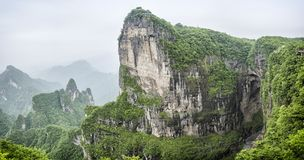 Panorama of the Tianmen Mountain Peak with a view of the cave Known as The Heaven`s Gate surrounded by the green forest and mist royalty free stock photos