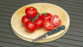 Panorama of tomatoes on cutting board with knife. Royalty Free Stock Photography