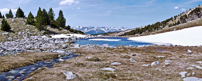 Panorama from top of Madriu-Perafita-Claror Valley in spring. The stream and the lake bordered with snow, the mountain chain of Andorran Pyrenees and the sky Stock Photography