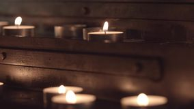 Church table for candles. Panorama from top to bottom with a change of focus from the candles at the top of the table to the candles at the bottom of the church stock video footage