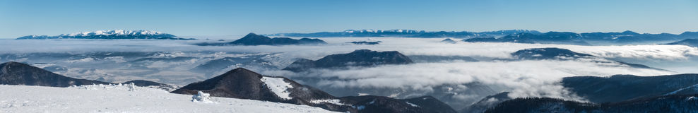 Panorama from top of winter mountain ridge above low clouds Stock Image