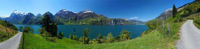 Panorama: traccia di escursione sul pendio di collina di un lago alpino circondato dai picchi bianchi Fotografia Stock Libera da Diritti