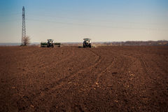 Panorama of tractor sowing in field Stock Photography
