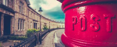 British City Post Box Panorama. Panorama Of A Traditional British Red Post Box In A Curved Edwardian Terrace Street With Shallow Depth Of Focus royalty free stock photo