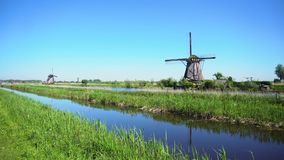 Dutch windmill over river waters. Panorama traditional dutch windmills rural scenery at Kinderdijk at summer day, Netherland stock video footage