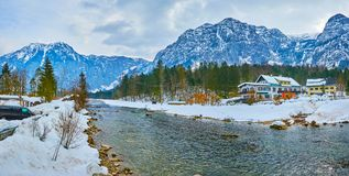Panorama of Traun river in Obertraun, Salzkammergut, Austria. The winter landscape of Obertraun village with huge mountains of Dachstein massif, old coniferous royalty free stock image