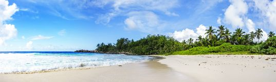 Panorama of tropical beach.palms,granite rocks and turquoise wat. Panorama of tropical beach with palm trees,granite rocks, white sand  and turquoise water Royalty Free Stock Photography
