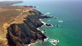 Panorama of tropical coastline cliffs. Impressive shot taken with drone and showing panoramic view of rough cliffs on tropical shoreline with blue ocean water in stock video footage