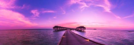 Panorama tropicale di tramonto Tiri il tramonto in secco nell'isola delle Maldive con le ville di lusso dell'acqua ed il pilastro Immagine Stock
