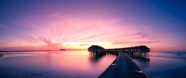 Panorama tropicale di tramonto Tiri il tramonto in secco nell'isola delle Maldive con le ville di lusso dell'acqua ed il pilastro Fotografia Stock
