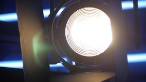 Panorama in a tv studio, spotlight is switching on in darkness. Close-up