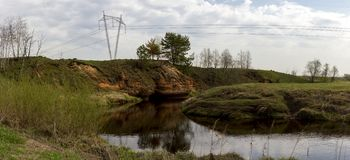 Panorama of the twisting abrupt coast of the small river with power lines. In summer cloudy day stock photography
