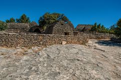 Panorama of typical hut made of stone with walled fence and sunny blue sky, in the Village of Bories, near Gordes. royalty free stock photo