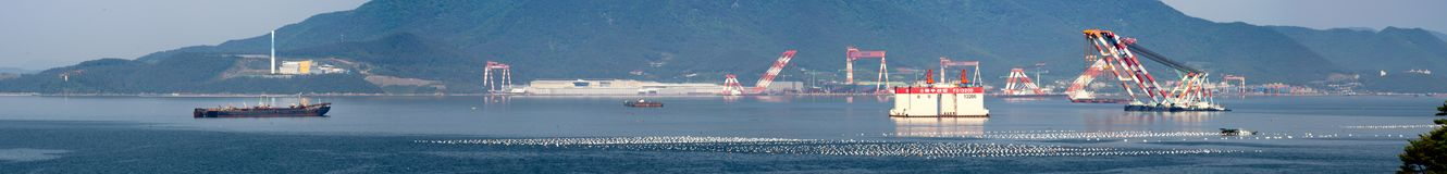Panorama of Under constructed off shore platform and crane barges anchor in the bay in front of Samsung Heavy Industries or SHI. GEOJE ISLAND, SOUTH KOREA - MAY royalty free stock image