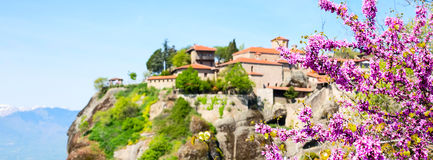 Panorama with unfocused Great Meteoro Monastery in Meteora and Branch of pink blossom Royalty Free Stock Photos