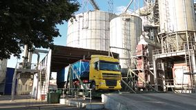 Panorama of unloading grain trucks at elevator on elevating hydraulic platform unloader. Grain crops transshipment at. Big sea terminal at seaport stock video footage