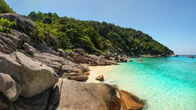 Panorama of unspoiled empty beach of Similan islands. With idyllic huge rocks, sun, jungle forest and turquoise green blue sea taken on sunny day. Phang Nga stock photo