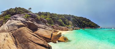Panorama of unspoiled empty beach of Similan islands. With idyllic huge rocks, golden sun, jungle forest and turquoise green blue sea taken on sunny day. Phang stock photography