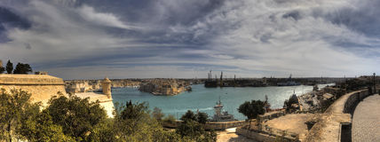 Panorama of the Valletta city harbor area at Malta, with many historic buildings along the coastline and a large park Stock Image