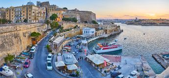 Panorama of Valletta fortifications, Malta. VALLETTA, MALTA - JUNE 17, 2018: The evening view on city walls, St Andrew`s Bastion, curved streets and ferry Royalty Free Stock Photo