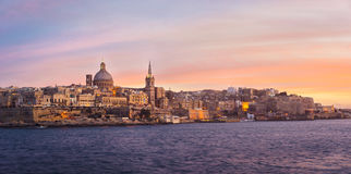 Panorama of Valletta at sunset, Malta. Valletta skyline at sunset with Basilica of Our Lady of Mount Carmel, viewed from Sliema, Malta Royalty Free Stock Image