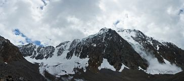 Panorama of valley with view to snow mountains and avalanche. Beautifull valley with view to snow mountains and avalanche in Altaj, Russia at the summer stock images