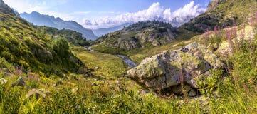 Panorama van berglandschap met weide, in een rivier wordt gevestigd die val Royalty-vrije Stock Afbeeldingen