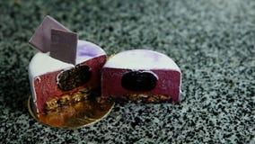 Panorama van besnoeiing in half purpere verglaasde mousse minicake stock videobeelden